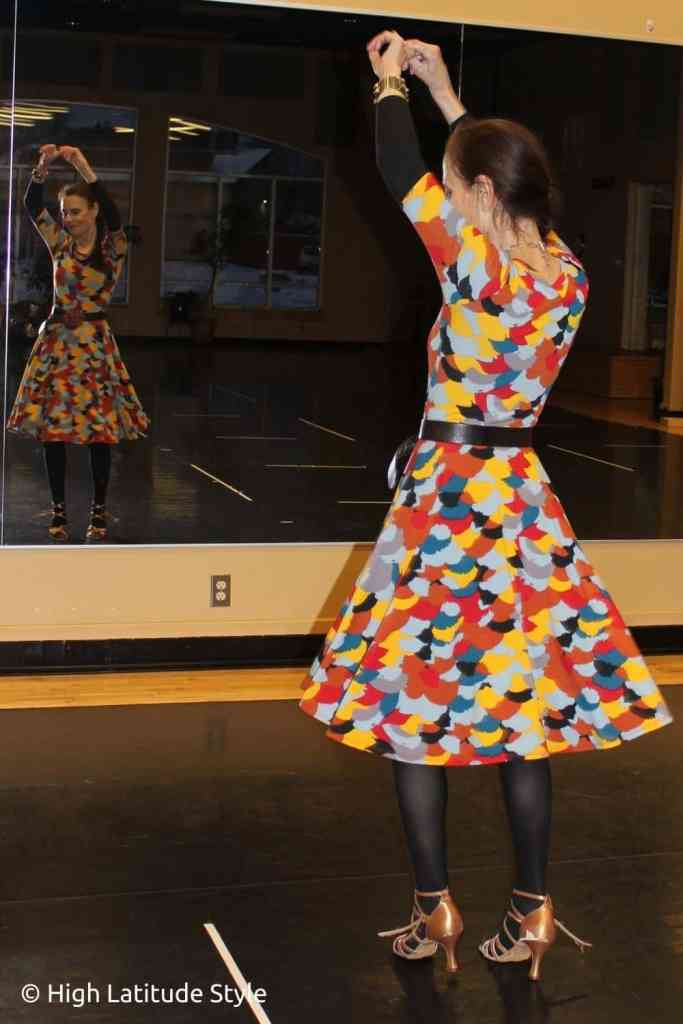 over 50 years old blogger exercising in a print dress in a dance studio