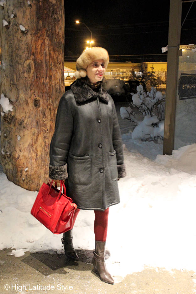 #fashionover40 mature woman in winter outfit with shearling coat, headband, tote and red booties
