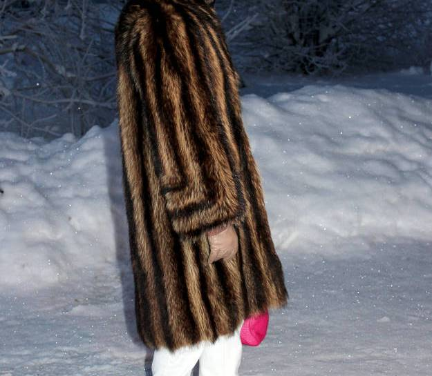 over 50 years old woman in white boyfriends and fur coat in winter