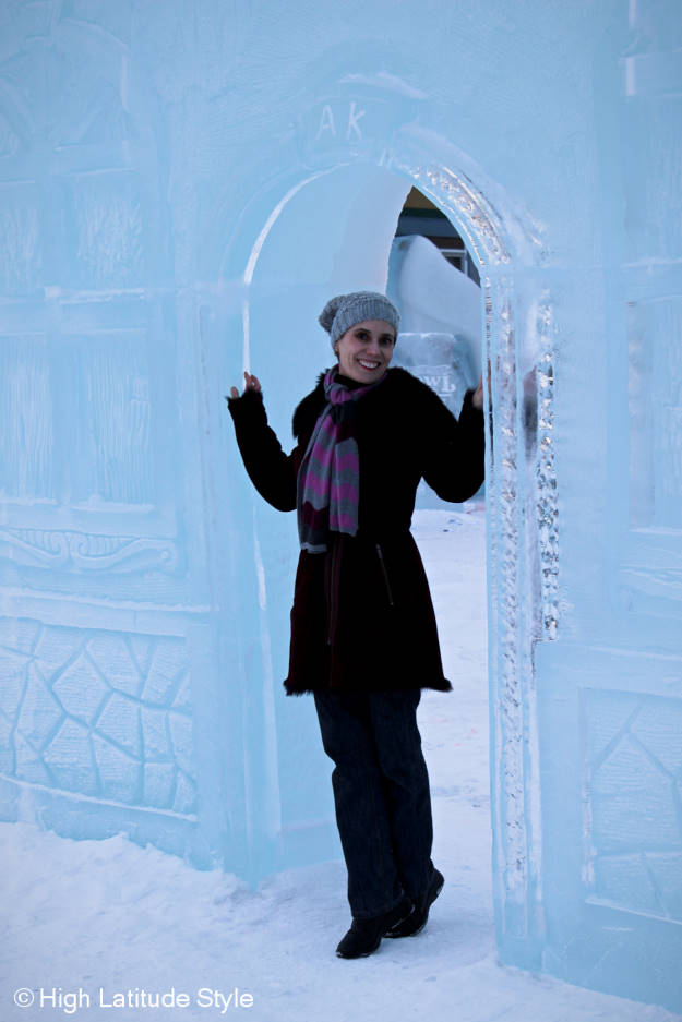 Alaskan fashion blogger posing for outfit photos in an ice door with ashearling motorcycle coat, chevron scarf, jeans, shearling booties and pom-pom hat