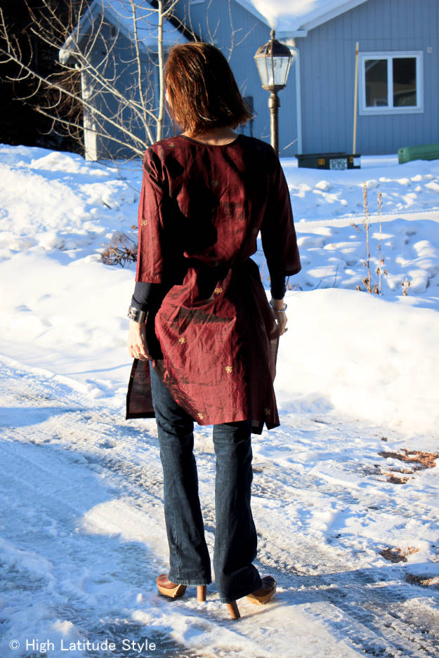 style blogger over 50 wearing a Bohemian style Indian long painted silk tunic over flared jeans