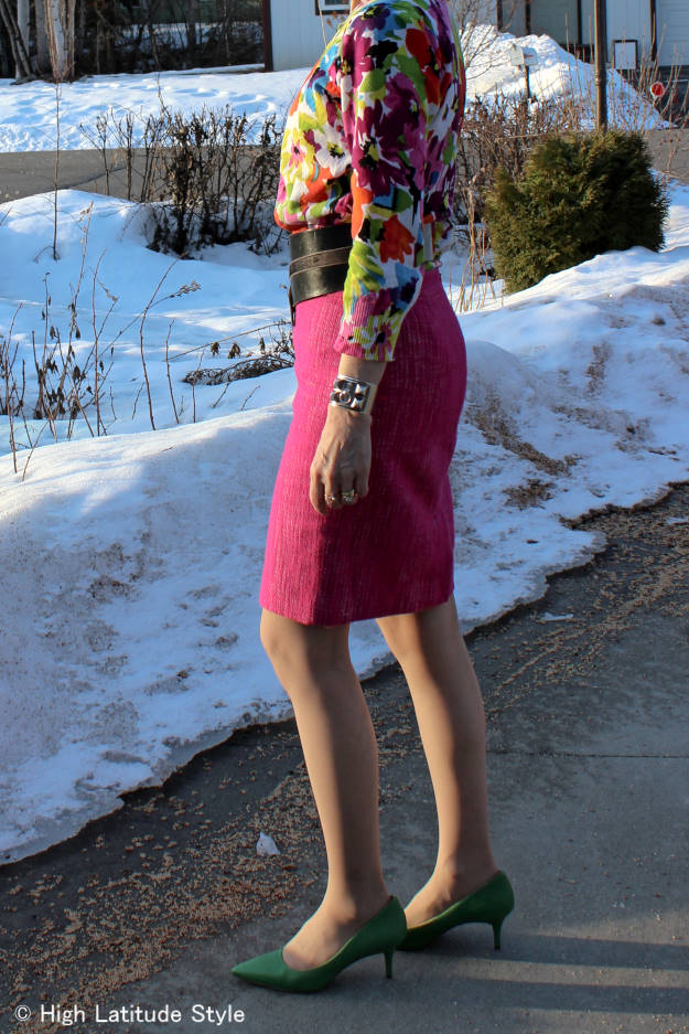 #fashionover50 style blogger Nicole in a spring outfit with floral top and pink skirt in Alaska