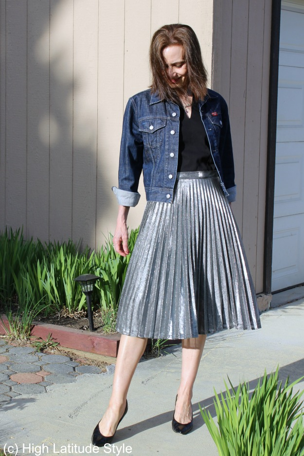 #styleover50 mature woman in silver pleated skirt with denim jacket and pumps