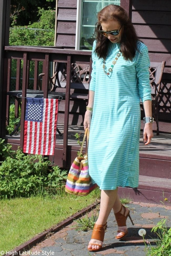 stylist wearing resort style with a green white stripe sunprotective dress, sunglasses, tan heels and striped fabric bag