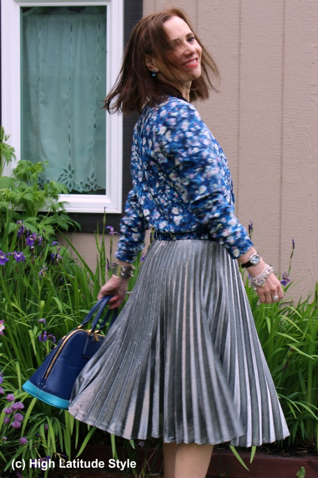 fashion blogger over 50 donning trendy silver pleated skirt with floral bomber