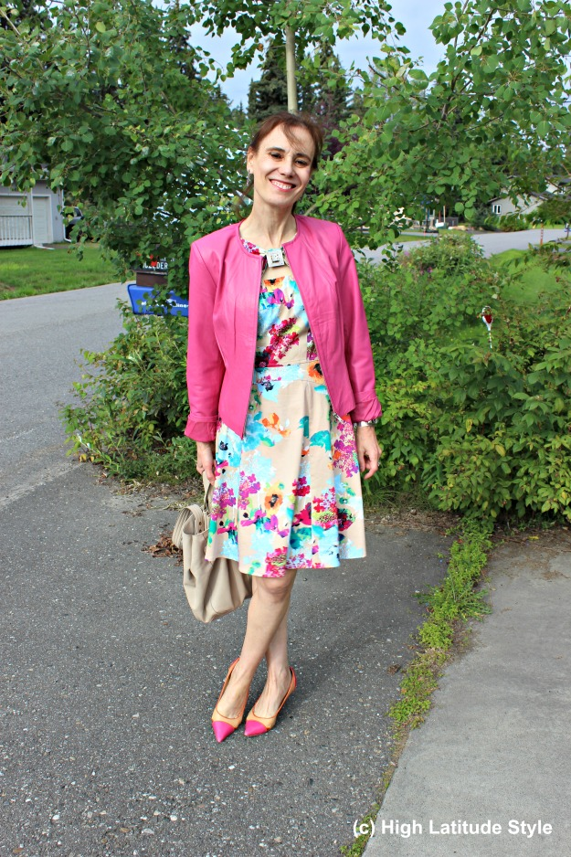 #fashionover50 mature woman in pink jacket and printed dress with rose and yellow