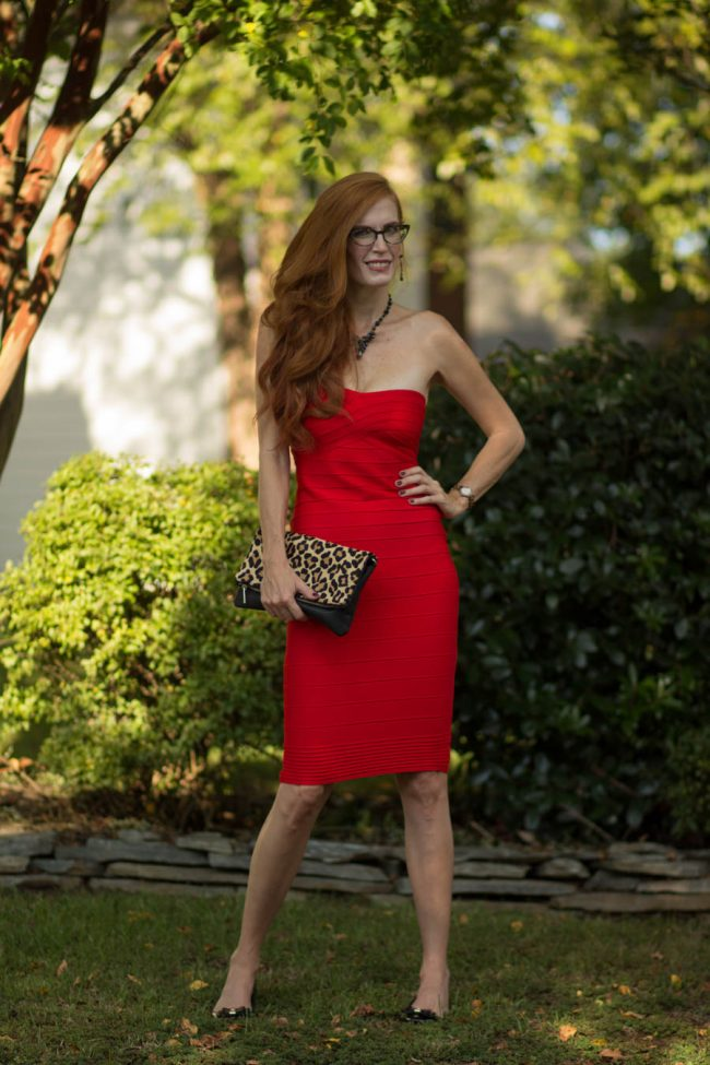 mature redhead wearing a little red dress with leopard print clutch