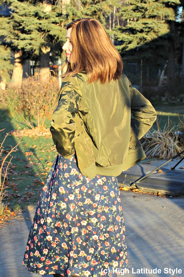 #fashionover50 blogger Nicole wearing a bomber jacket over floral print dress