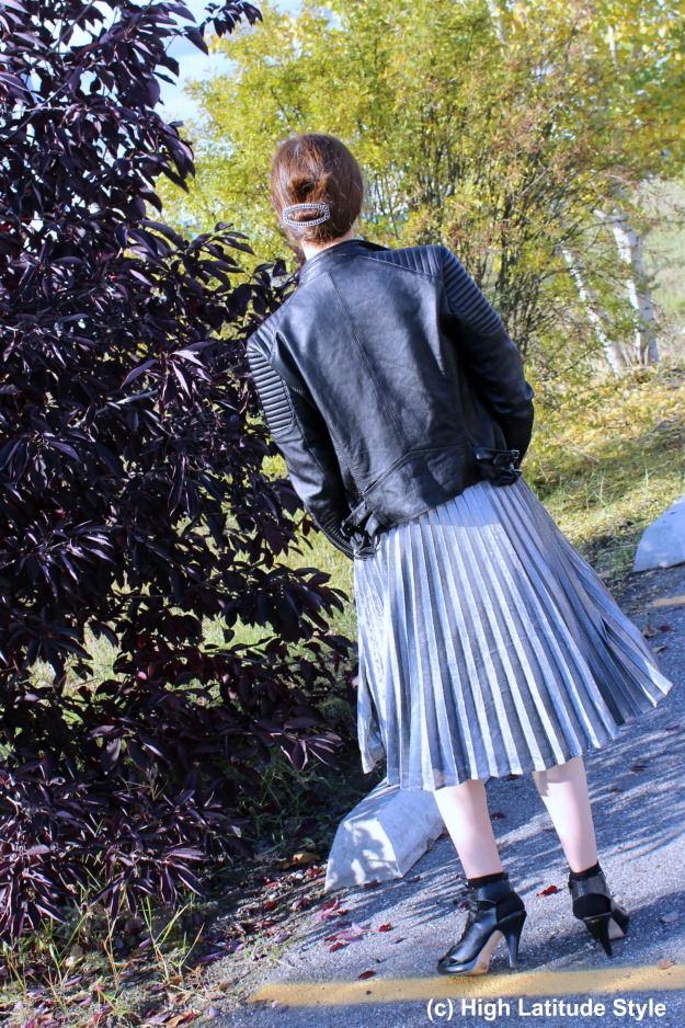 #styleover50 woman in silver pleated skirt and leather jacket