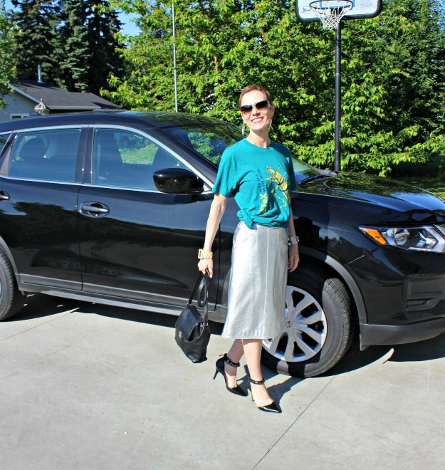 mature woman in front of a brand new car