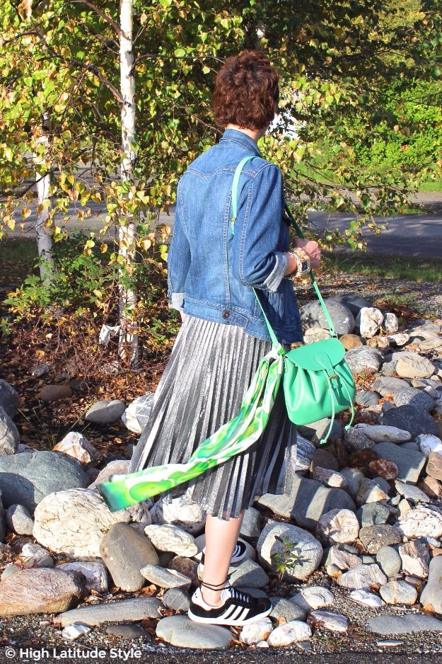 #fashionover50 style blogger Nicole with pleated silver skirt, denim jacket green scarf and bag