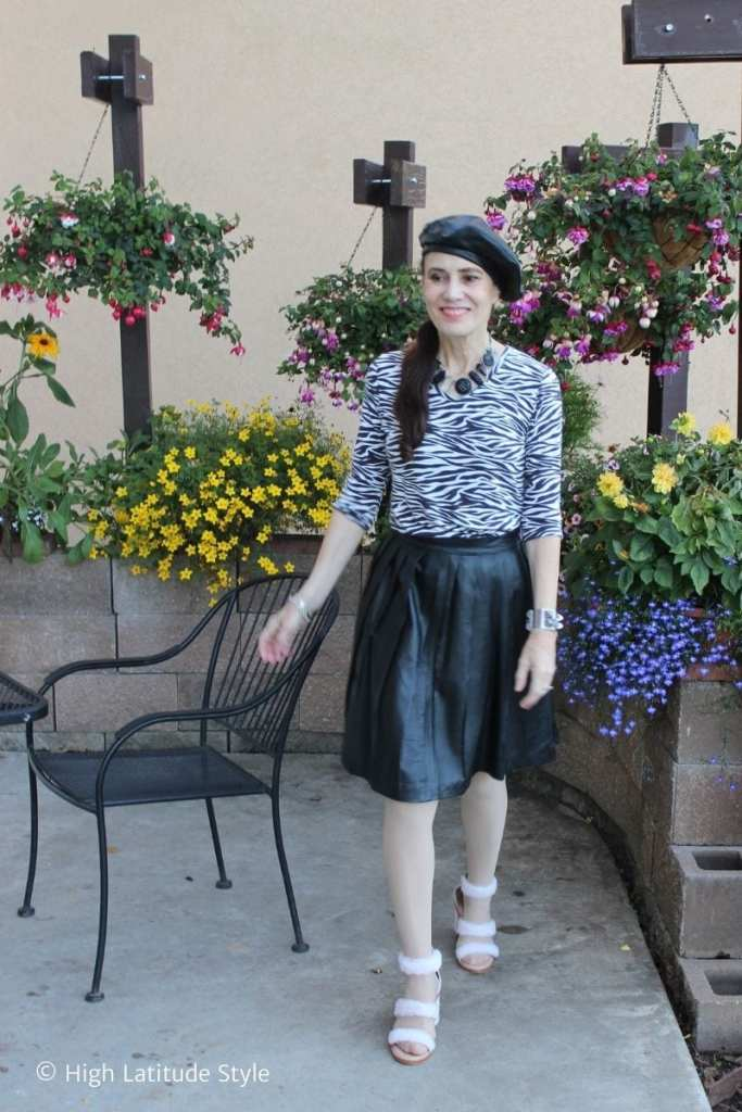 influencer in pleated leather skirt, leather beret and zebra top, fall sandals