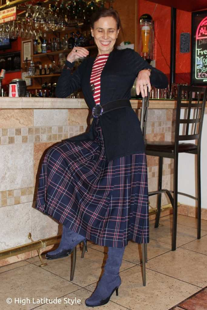over 50 years old blogger in pleated wool skirt, long cardigan, suede boots striped top sitting on a stool