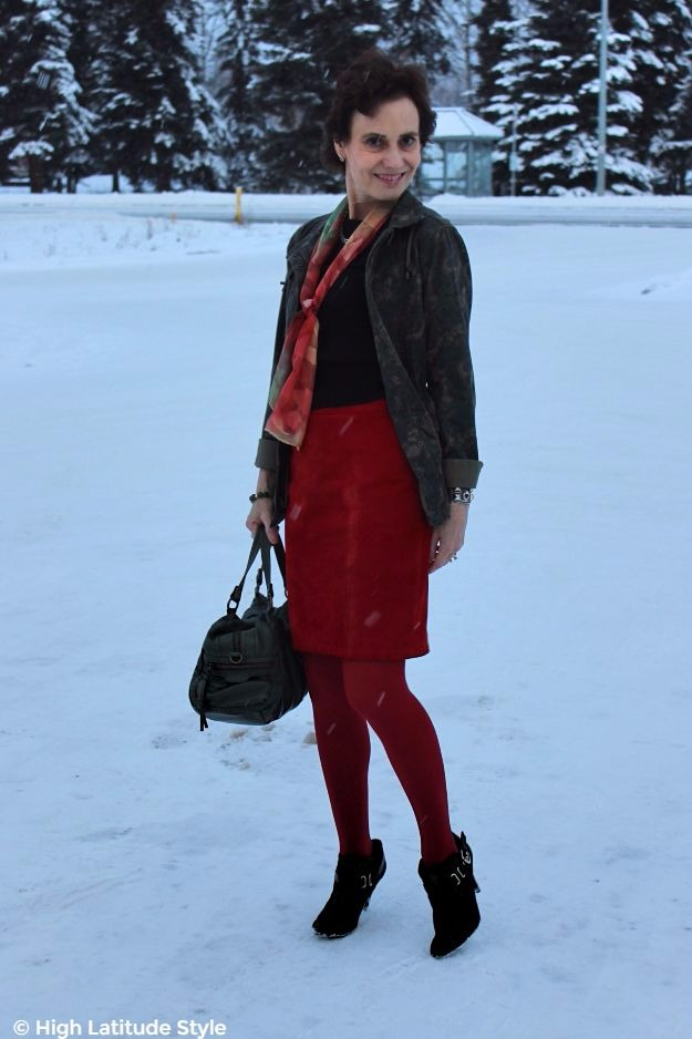 midlife woman in heels on snow in red and olive winter Casual Friday look