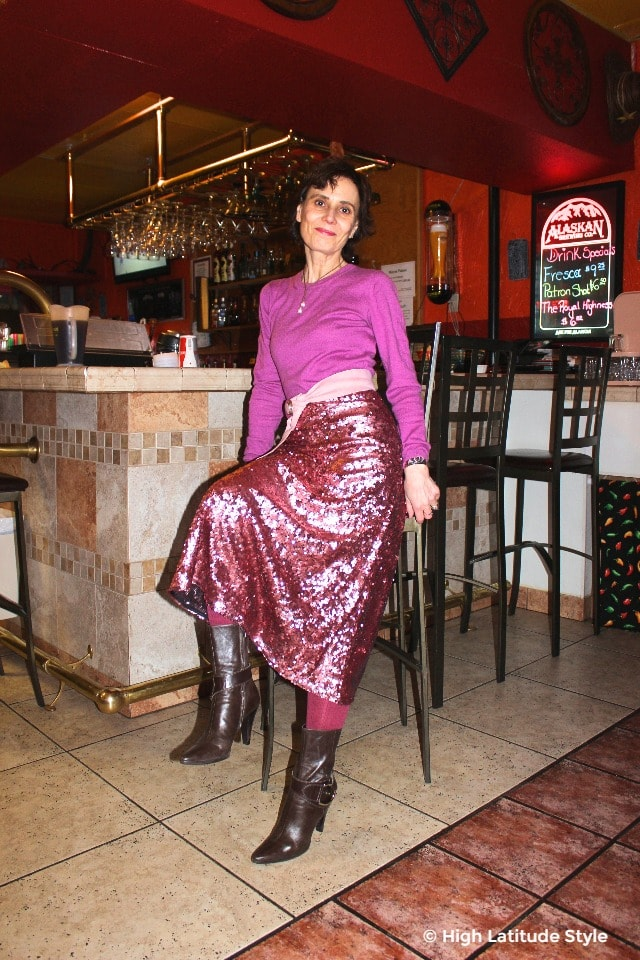 #midlifestyle mature woman sitting at the bar of a restaurant in pink and brown look