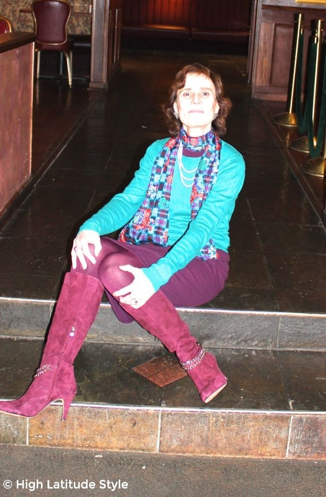 #fashionover50 woman sitting on stairs in an outfit with teal sweater, burgundy sheath dress, tight and boots