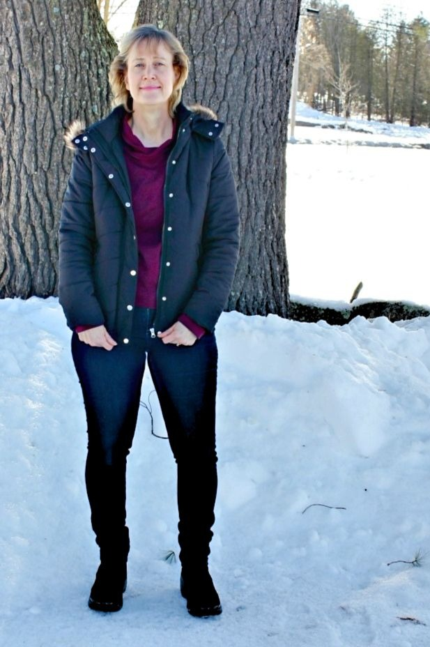 Ellen Christian in supportive boots, hooded puffer anorak, jeans, and sweater combo