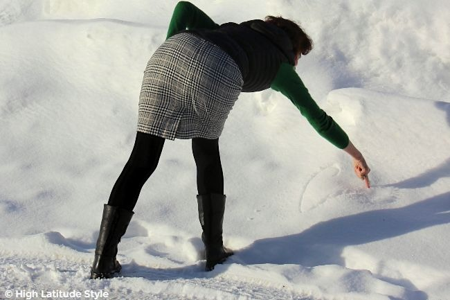 #springfashion Alaskan woman drawing in the snow in plaid skirt meadow color sweater