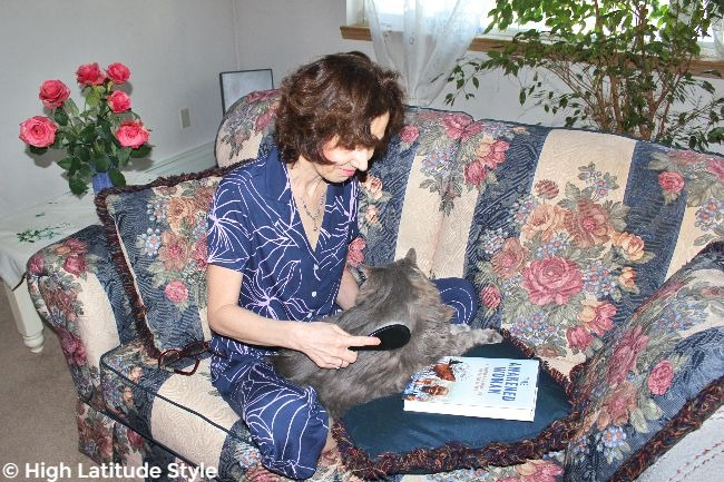 #advancedstyle midlife woman in PJs brushing a cat while sitting on a coach