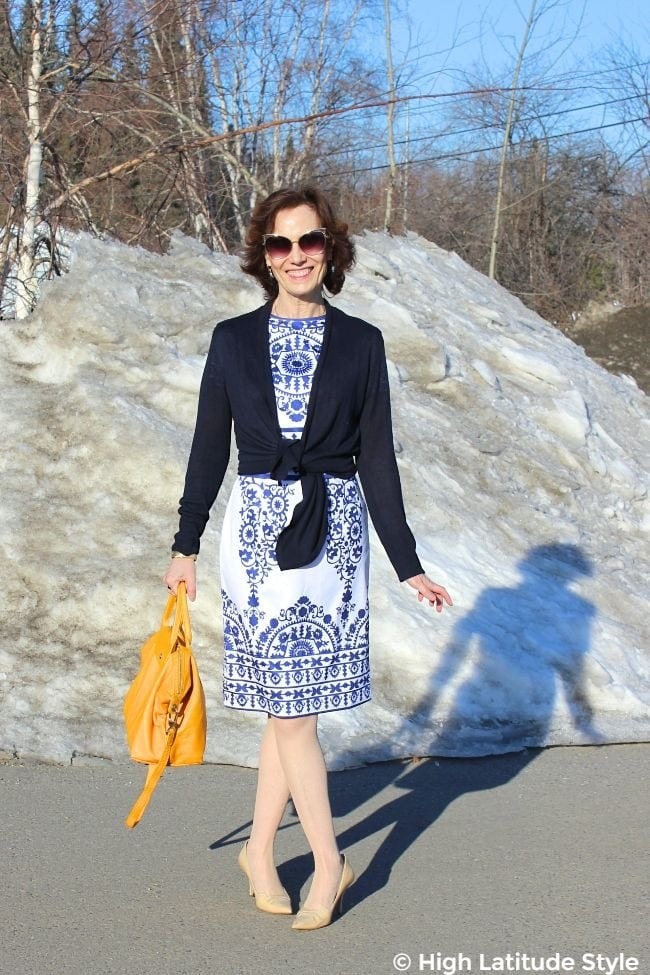 #fashionover50 female scientist in blue-white dress, blue cardigan with nude pumps and yellow bag