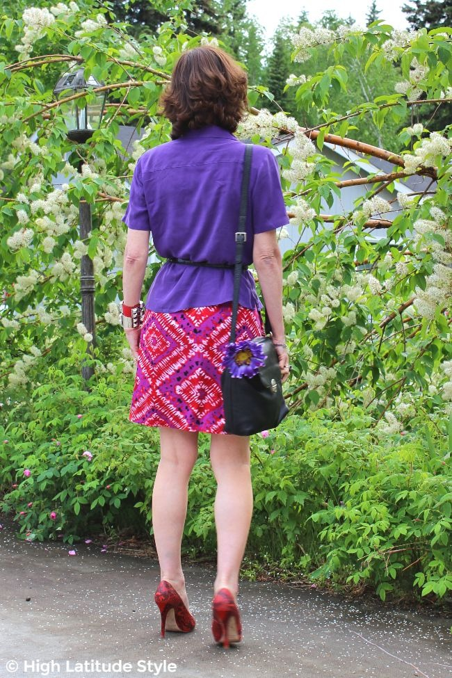mature woman in faux printed skirt and shirt with belt, messenger and silk flower