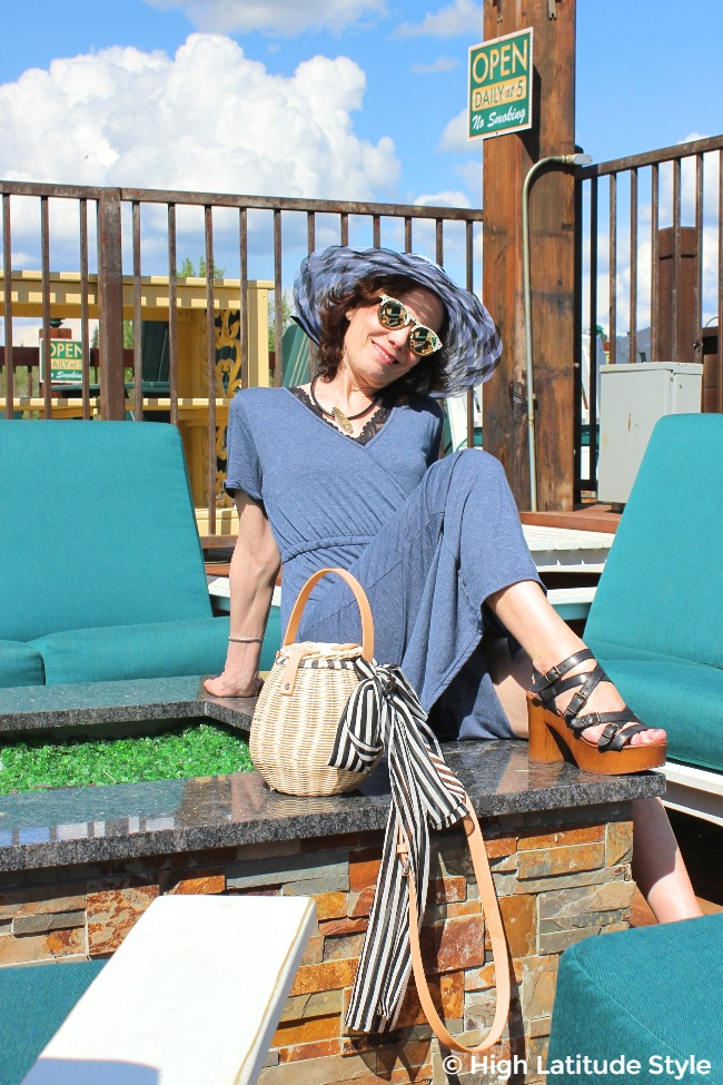 midlife blogger in maxi dress, hat, wood sandals with accesorized trendy basket bag
