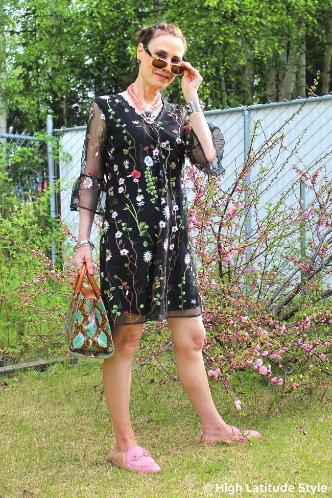 fashion advice blogger in a trendy A-line floral dress accessorized with sunglasses and floral statement necklace
