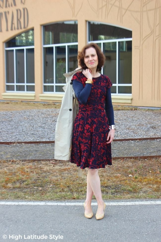 midlife blogger in floral jersey dress with pointy toe heels and trench coat for a work trip