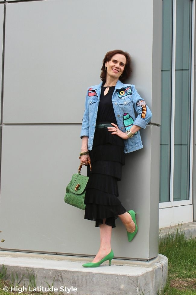 over 50 years old fashion blogger in street style outfit with sequins, pleats, denim and black