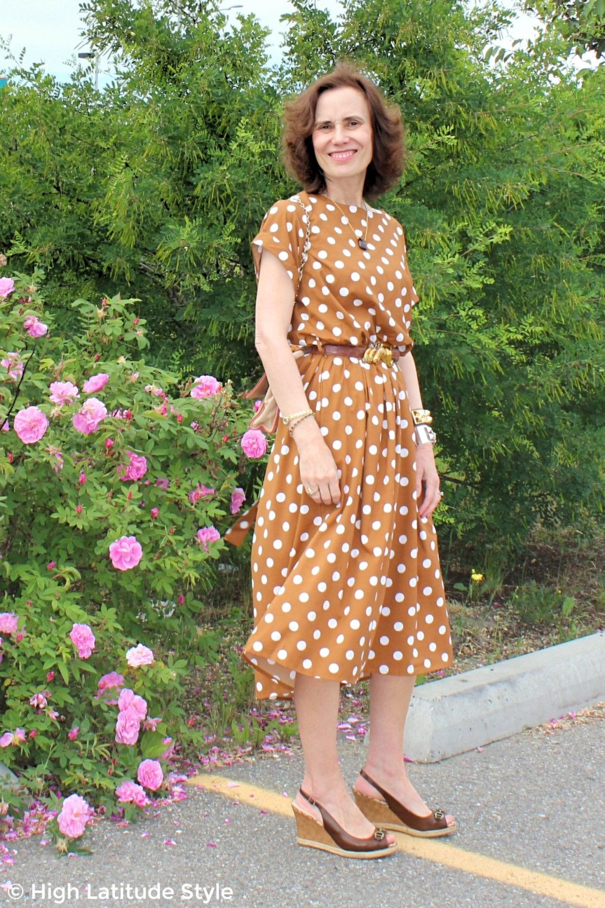 style blogger in summer outfit with polka dots in front of Sitka roses