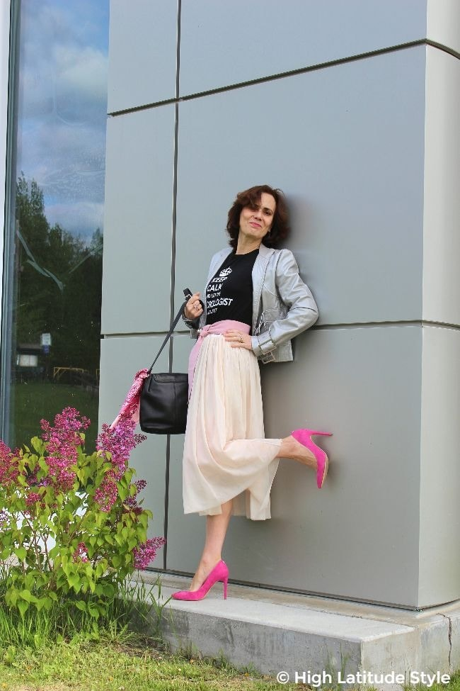 #fashionover50 mature street style blogger in blush mesh skirt, pink shoes and belt, graphic tee and silver biker jacket posing at a silver wall