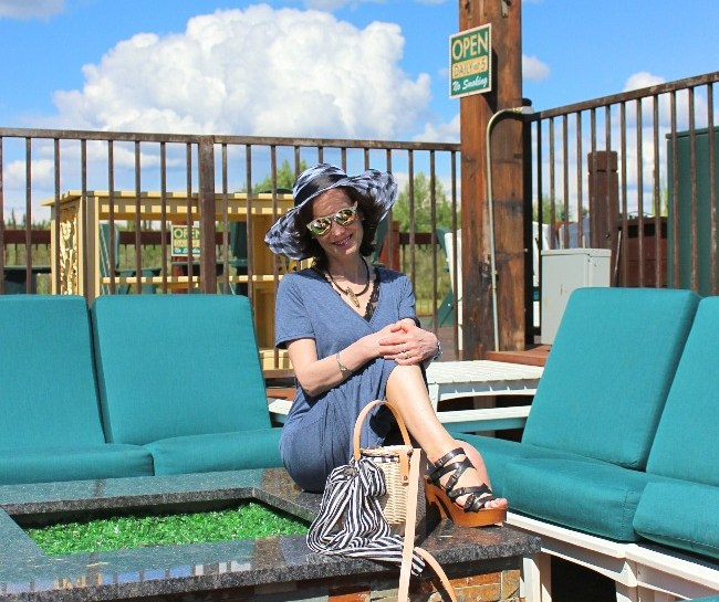#vacationstyle #resortstyle woman lounging on a deck in a maxi v-neck knitdress, sandals and sunhat