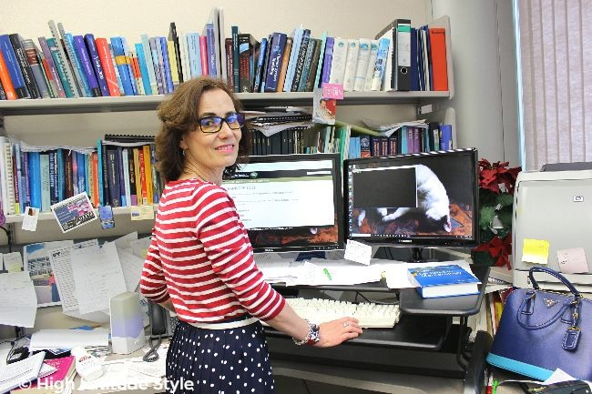 #fashionover50 woman at work wearing eye-protective glasses, a striped top and pollka dot skirt