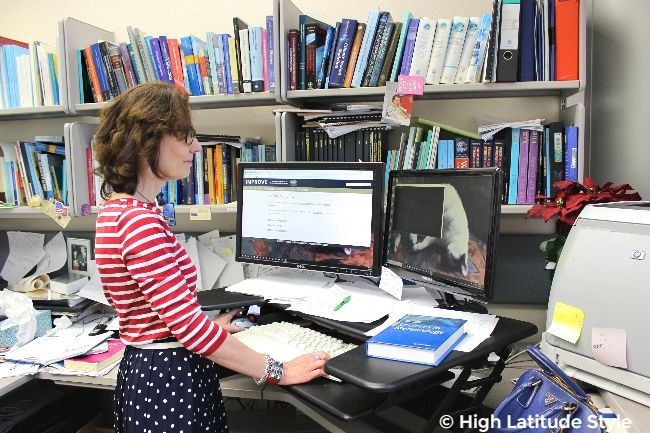 #styleover50 older lady in her office with striped top, dotted skirtwaering computer glasses