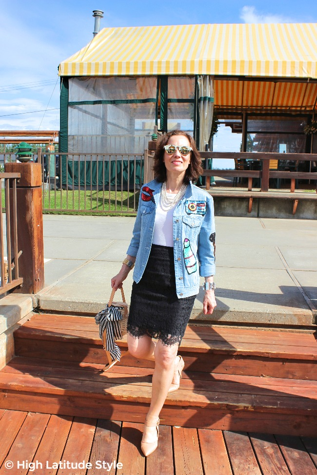 #fashionover50 midlife woman in lace skirt, sequin patch denim jacket, nude pumps and mirrored sunglasses