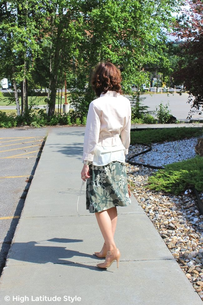 #advancedstyle back view of woman in a summer outfit of floral skirt with blush utility jacket