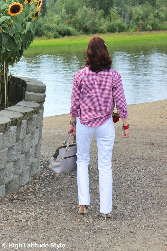 #styleover50 back view of an older woman standing at the Chena in white jeans and a plaid shirt