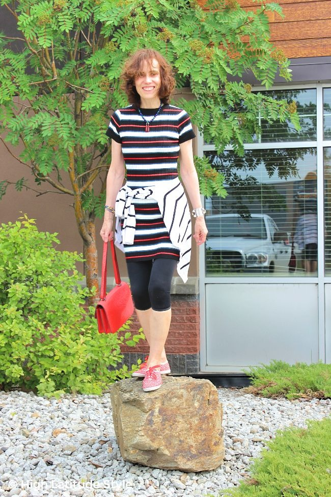 older lady in black red green white striped dress