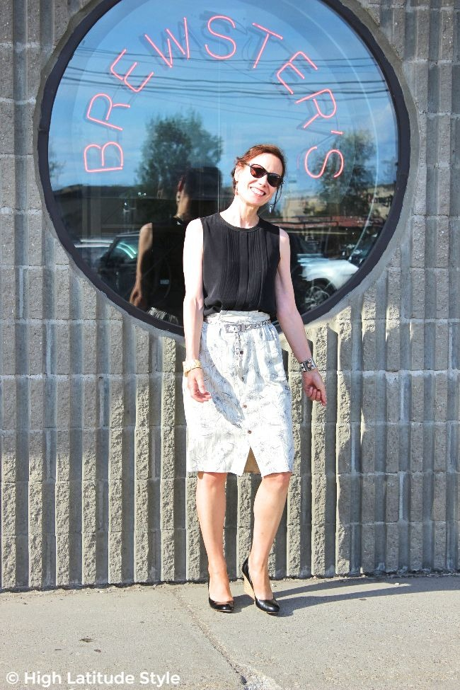 #fashionover50 mature woman in straight summer skirt with sleeveless top, sunglasses and wedge heels