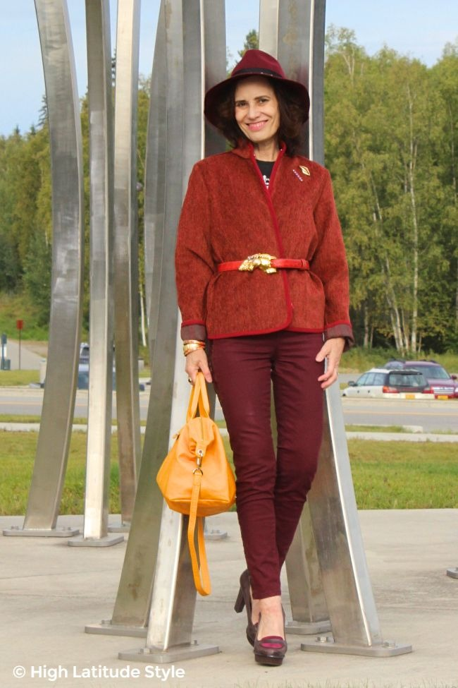 fashion blogger over 50 with a Tenth Street fedora, burgundy jeans and jacket plus yellow pliage