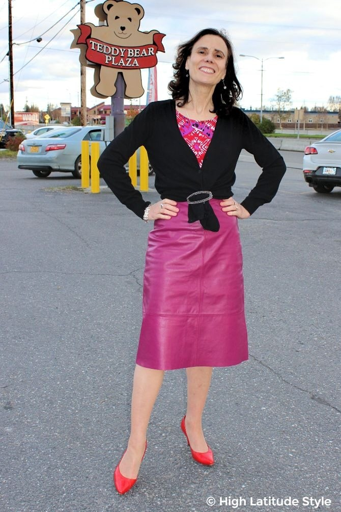 #fashionover50 fashion blogger donning a work outfit with fuchsia skirt, printed top,, black cardigan and red pumps