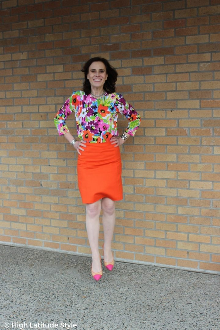 blogger Nicole jumping in a floral top, straight knee-length skirt, pantyhose, and heels