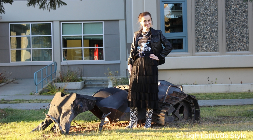 blogger Nicole in an edgy look with aviator jacket, pleated skirt, graphic Tee and statement boots