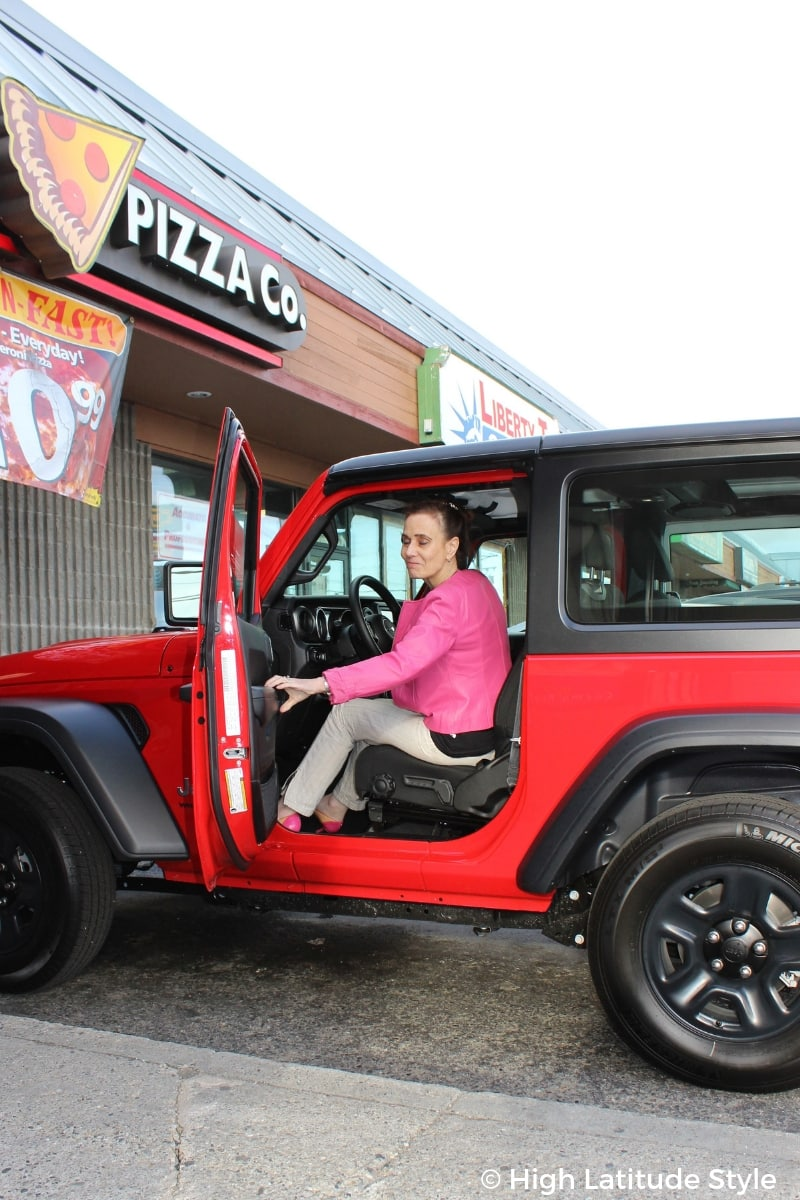 over 50 years old fashion blogger Nicole in summer to fall transition casual outfit closing the door of a Jeep Wrangler in pants, and motorcycle jacket
