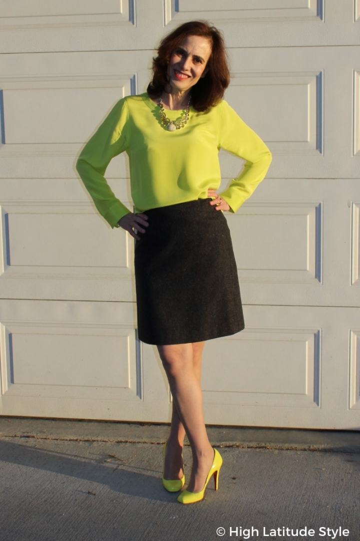 #over50fashion style blogger Nicole in gray above the knee skirt, neon yellow top and heels with yellow statement necklace