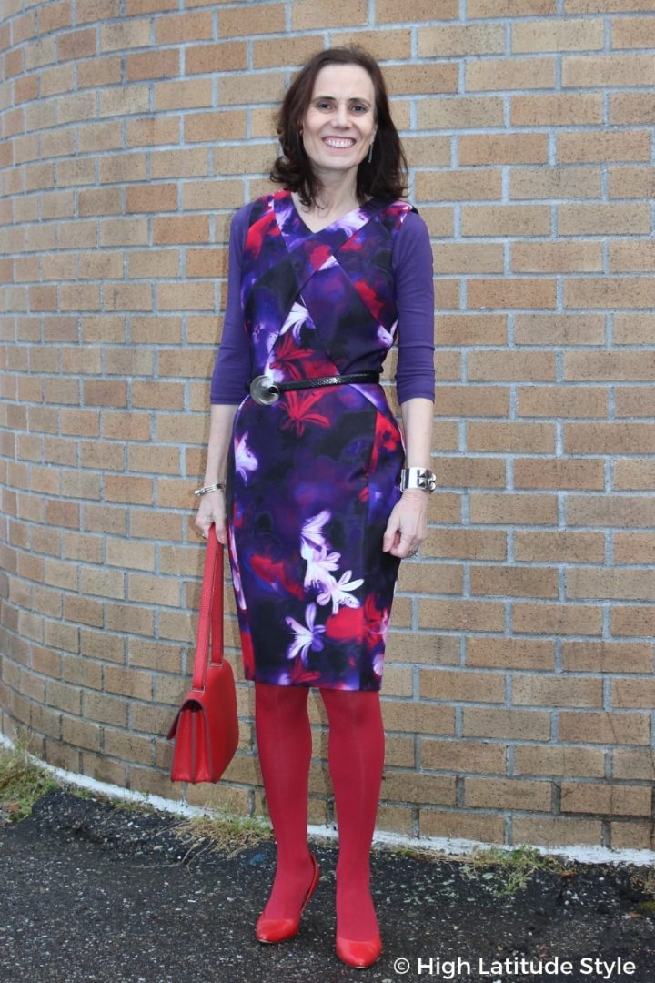 #fashionover50 style blogger in purple print sheath, red tight, pumps, and bag