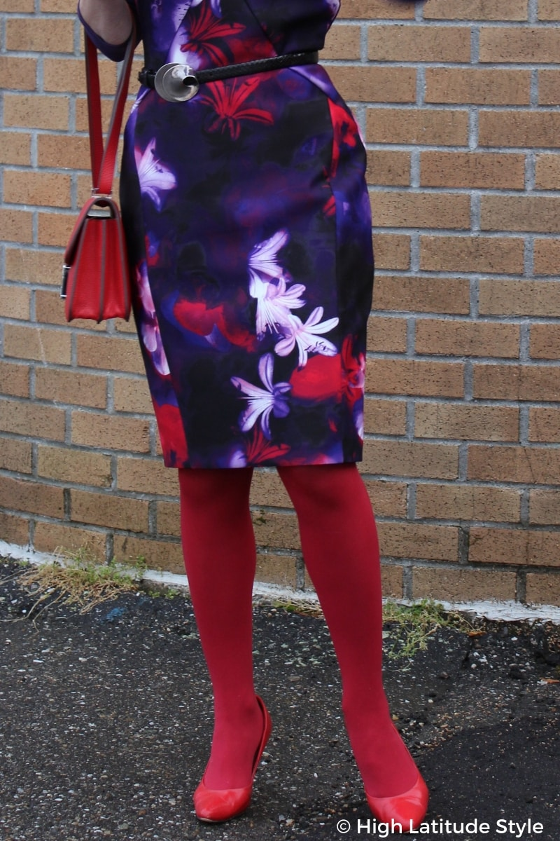 details of purple flattering scuba dress sheath with red and white floral print, statement belt, tights, pumps and bag