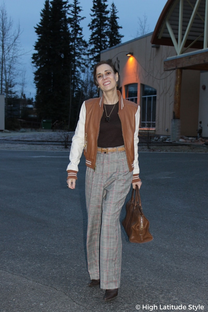 Nicole of High Latitude Style in wool pants, cream and brown jacket, chocolate sweater and booties brown tote in front of night sky