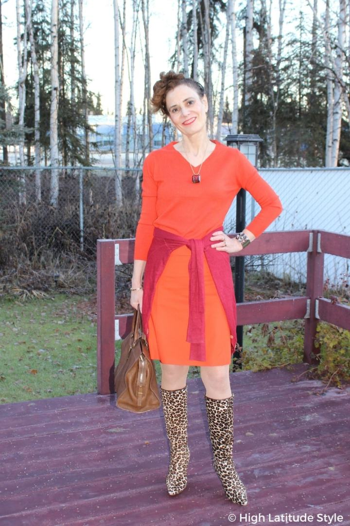midlife style blogger in business casual work outfit with skirt, top, cardigan and leo print boots