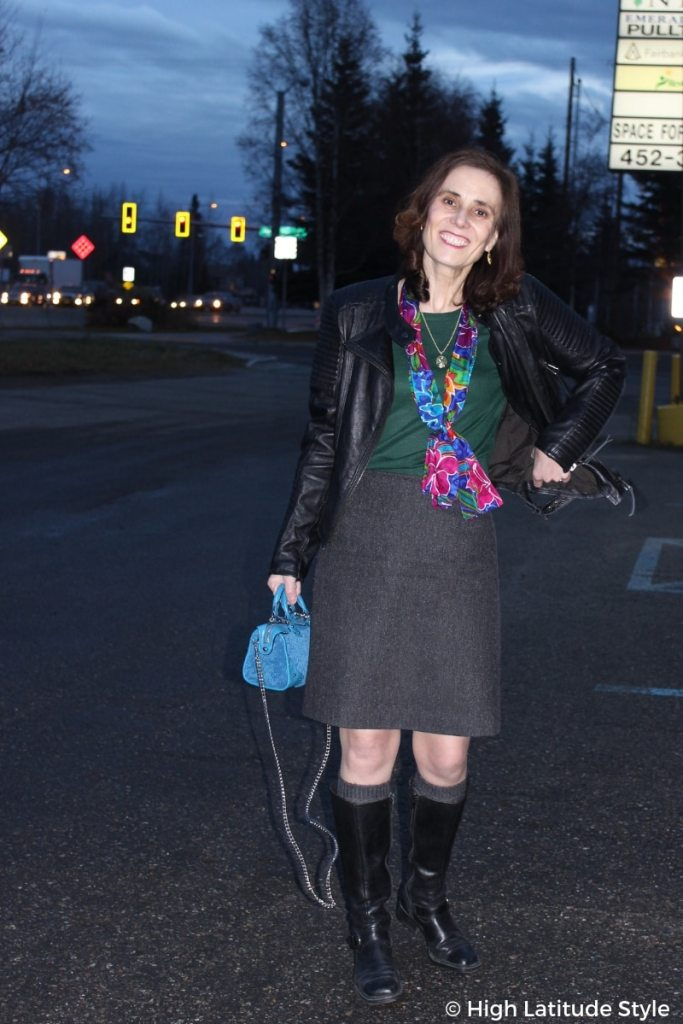 fashion blogger in tweed skirt, leather jacket, sweater, riding boots, scarf and shearling mini crossbody